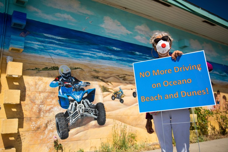 Oceano resident Lucia Casalinuovo, an activist against off-roading, carries a sign next to a mural depicting the the vehicles she is protesting on July 21, 2020. Photo by Brittany App for CalMatters