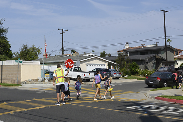 A crossing guard ushers Mcgaugh Elementary School students across the street in Seal Beach, CA. Sept. 17, 2020. Los Alamitos Unified School District has been permitted to to reopen elementary schools for hybrid in-person instruction. Photo by Tash Kimmell for CalMatters