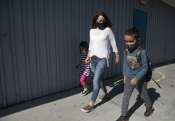 Special education instructor Liz Duffield walks her pre-k and kindergarten-aged students to the pick up area at the end of the school day on Oct. 27, 2020. Duffield was able to resume in-person instruction last week. Photo by Anne Wernikoff for CalMatters