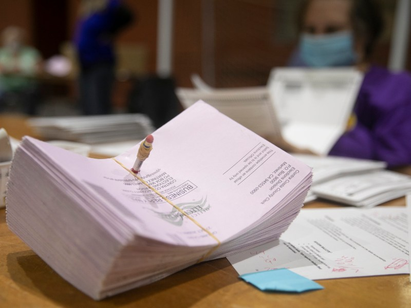 A stack of mail-in ballots on a table at a ballot extraction facility in Martinez on Oct. 31, 2020. By Halloween, Contra Costa County had already received more ballots than the total number in the March primary. Photo by Anne Wernikoff for CalMatters