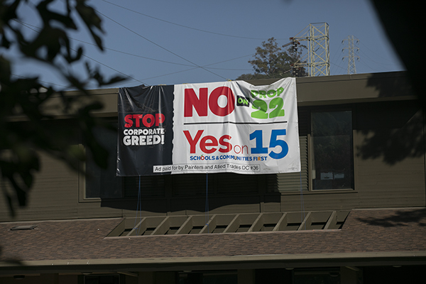 A banner sponsored by Painters and Allied Trades Union hangs from a building on Martinez days before the election on Oct. 31, 2020. Photo by Anne Wernikoff for CalMatters