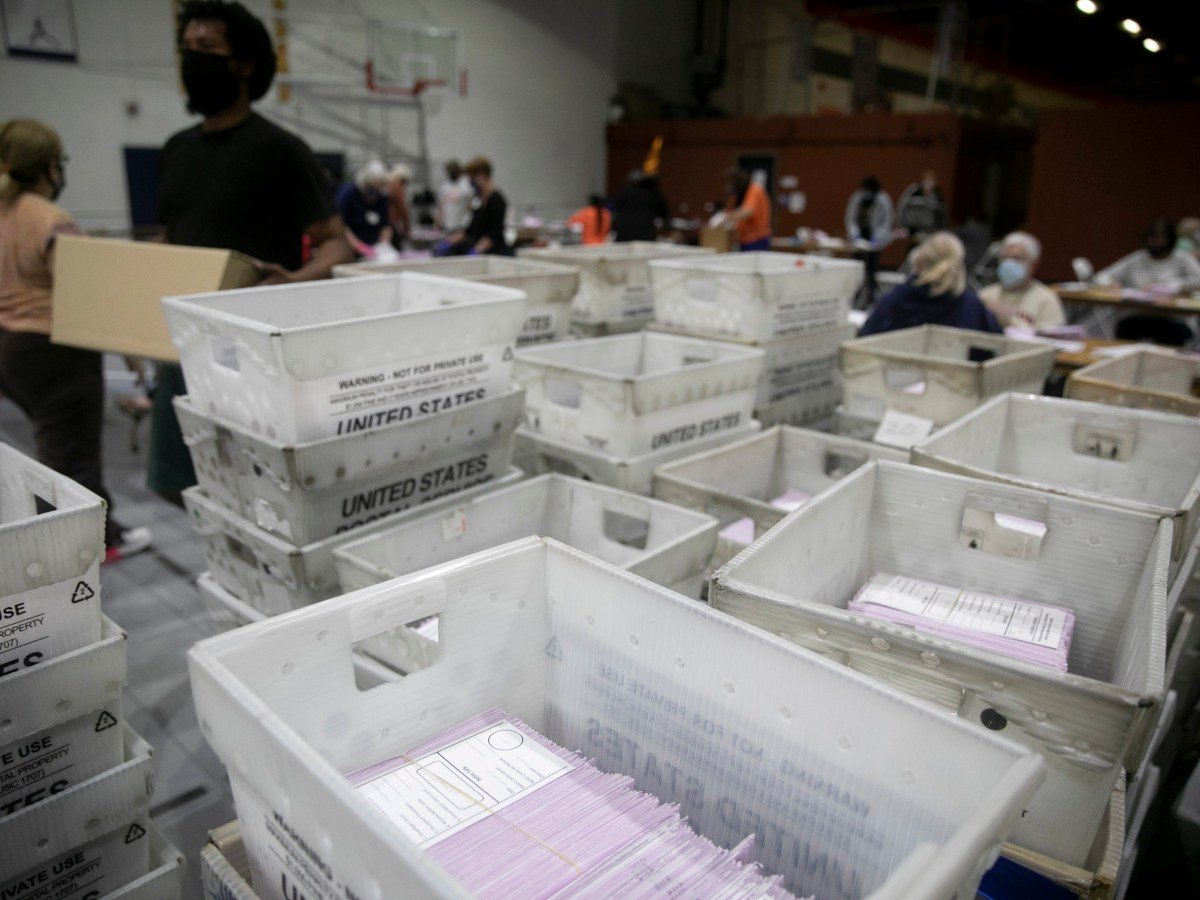 Dozens of volunteers extract ballots at the sports complex in Martinez on Oct. 31, 2020. Photo by Anne Wernikoff for CalMatters