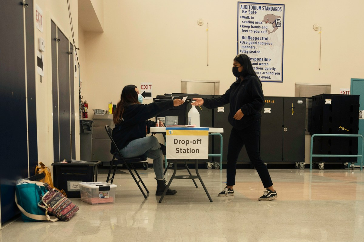 """A voter gets an """"I voted sticker"""" at the Los Angeles Elementary School polling place on Nov. 3, 2020. Photo by Tash Kimmell for CalMatters."""