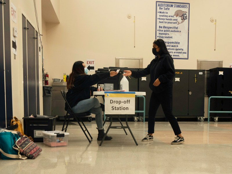 "A voter gets an ""I voted sticker"" at the Los Angeles Elementary School polling place on Nov. 3, 2020. Photo by Tash Kimmell for CalMatters."
