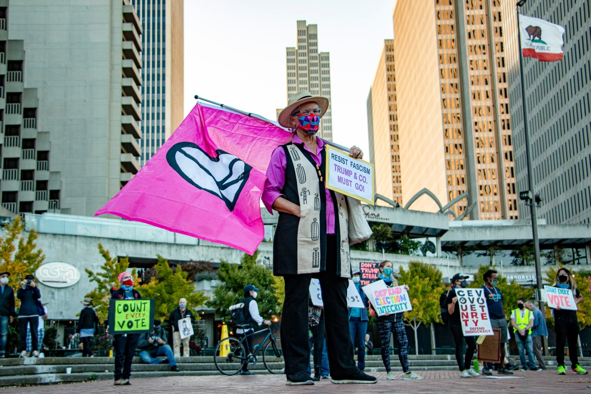Martha Hubert, a CodePink organizer, waves a peace flag a Nov. 4 rally in Embarcadero Plaza in San Francisco. Hubert said she feared violence may break out as election controversy escalated. Photo by Brian Howey for CalMatters