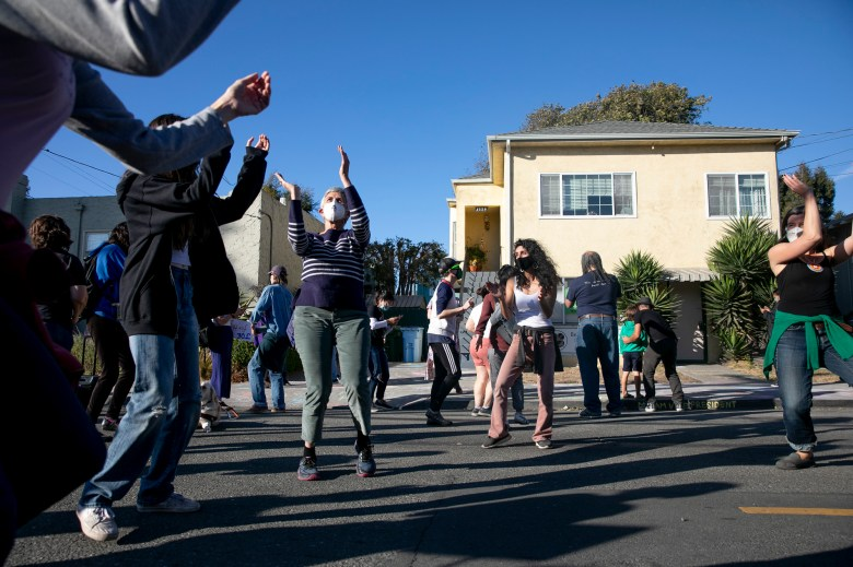 Linda Carr, left, dances to Michael Jackson's 'Can't Stop Till You Get Enough' in front of Vice President Elect Kamala Harris' childhood home in Berkeley on Nov. 7, 2020. Dozens gathered in the residential neighborhood to celebrate the Biden Harris win. Photo by Anne Wernikoff for CalMatters