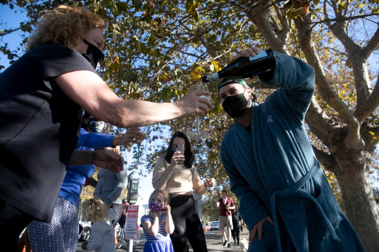"Ryan Frank, who lives near the lake, pours champagne for a fellow-reveler as a small group assembled to celebrate Joe Biden and Kalama Harris winning the presidency at Lake Merritt in Oakland on Nov. 7, 2020. ""We all started screaming, got out of bed in whatever we were wearing and the mimosas came out,"" said Frank of his bathrobe. Photo by Anne Wernikoff for CalMatters"