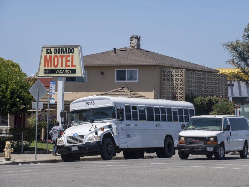 Un autobús estacionado en frente de El Dorado Motel deja a los trabajadores agrícolas, mientras que una camioneta que también transporta a los trabajadores agrícolas conduce justo al lado en Salinas el 1 de agosto de 2020. Foto de David Rodríguez, The Salinas Californian