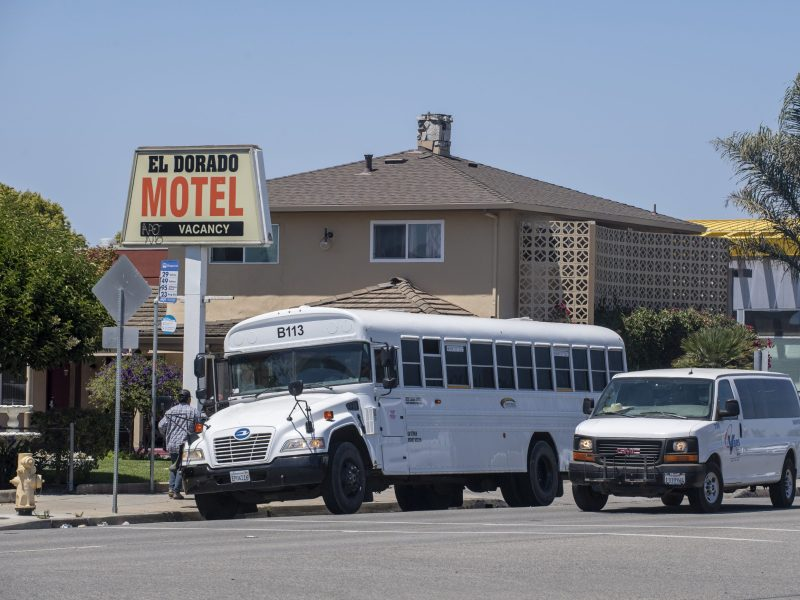 A bus parked in front of El Dorado Motel drops off farmworkers as a van that also transports farmworkers drives right next to it in Salinas on Aug. 1, 2020. Photo by David Rodriguez, The Salinas Californian