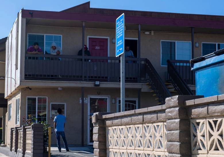 A few H2A workers hanging out n the second floor of the Budget Inn Motel in Salinas talk to a person standing just right outside their room on April 2, 2020. Photo by David Rodriguez, The Salinas Californian