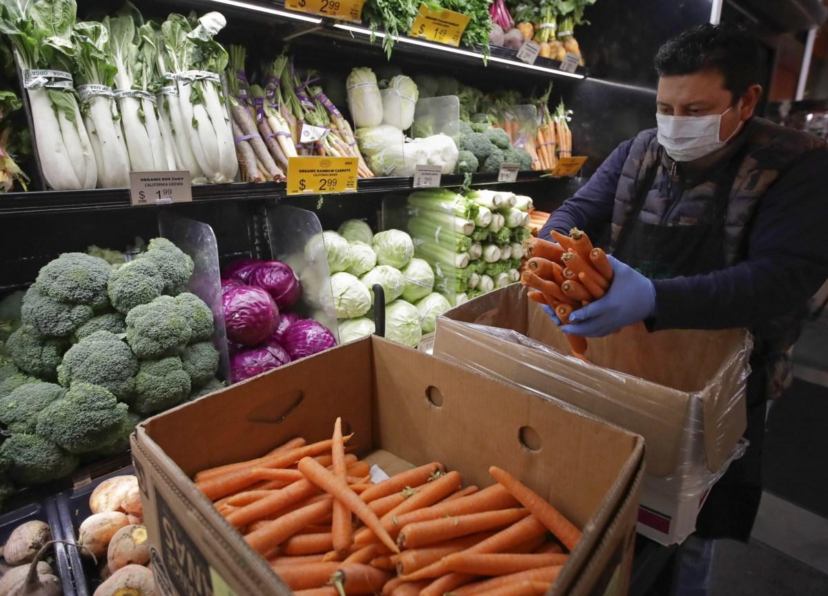 Los trabajadores de supermercados de California están presionando para que las tiendas restauren la 'paga de héroe' a medida que la pandemia se prolonga. En esta foto de archivo, un trabajador enmascarado almacena productos en el mercado Gus's Community Market en San Francisco. Foto de Ben Margot, AP Foto