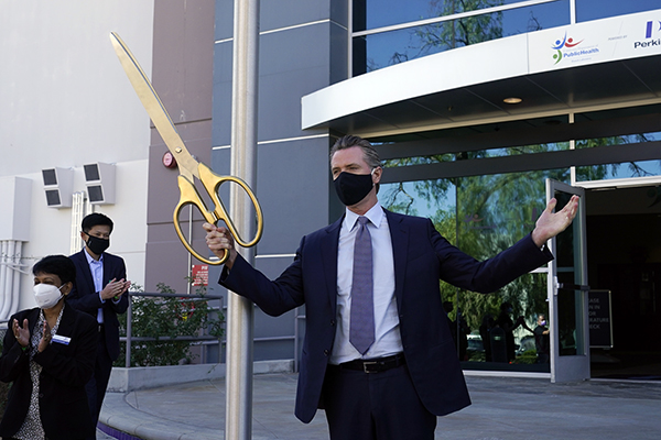 Gov. Gavin Newsom participates in a ribbon cutting ceremony at a COVID-19 testing facility Oct. 30, 2020, in Valencia. The state is working with corporate partner PerkinElmer to run the lab which will enable the state to process an additional 150,000 COVID-19 tests per day. Photo by Marcio Jose Sanchez, AP Photo/Pool