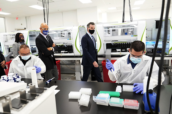 Gov. Gavin Newsom, center, tours a COVID-19 testing facility with Secretary of the Government Operations Agency Yolanda Richardson, far left, and Secretary for the California Health and Human Services Agency Dr. Mark Ghaly, second from left, Oct. 30, 2020, in Valencia. Photo by Marcio Jose Sanchez, AP Photo/Pool