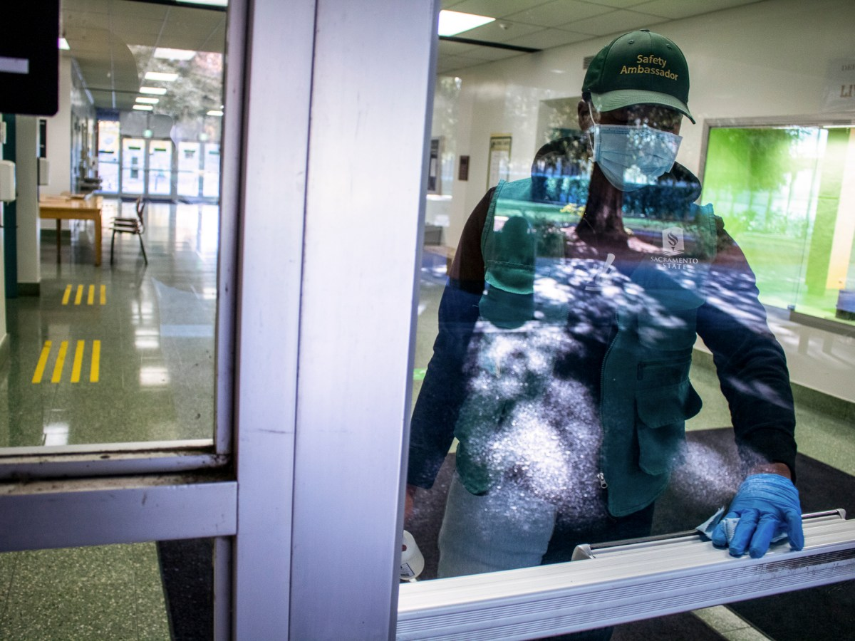 Daveion Harris, a Sac State Child Development Major, wipes down the entrance of Sequoia Hall at California State University, Sacramento on Dec. 2, 2020. Harris works as a student safety ambassador, ensuring cleanliness towards preventing the spread of the COVID-19. Photo by Rahul Lal for CalMatters