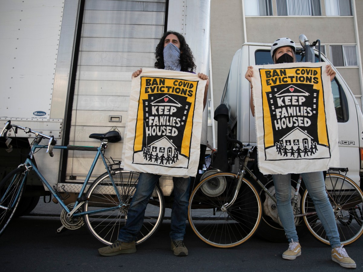 Galen Mancino, left, and Betsy Kinsey, hold up banners during a housing justice demonstration in the Adams Point neighborhood of Oakland on Dec. 5, 2020. Photo by Anne Wernikoff for CalMatters