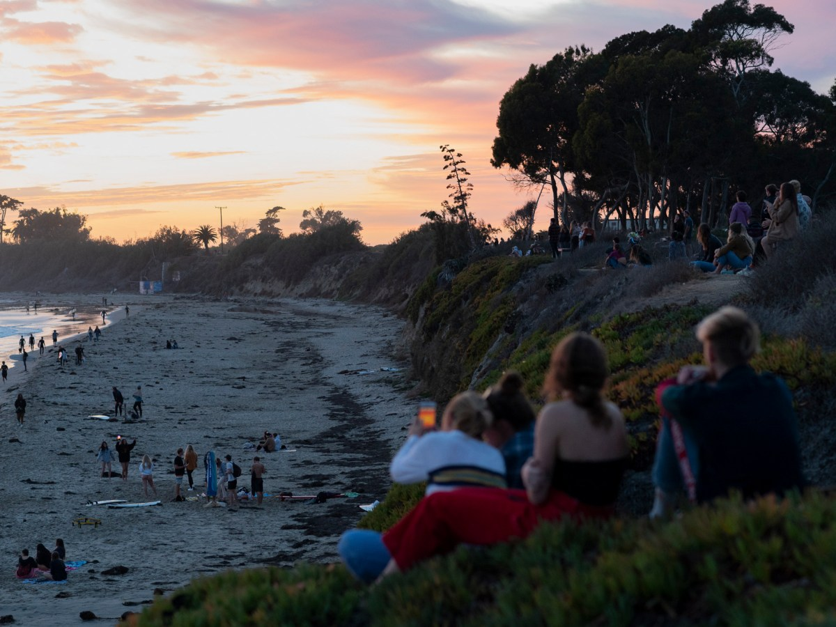 People gather near the cliffs as the sun sets in Isla Vista on Dec. 8 2020. Photo by Max Abrams for CalMatters