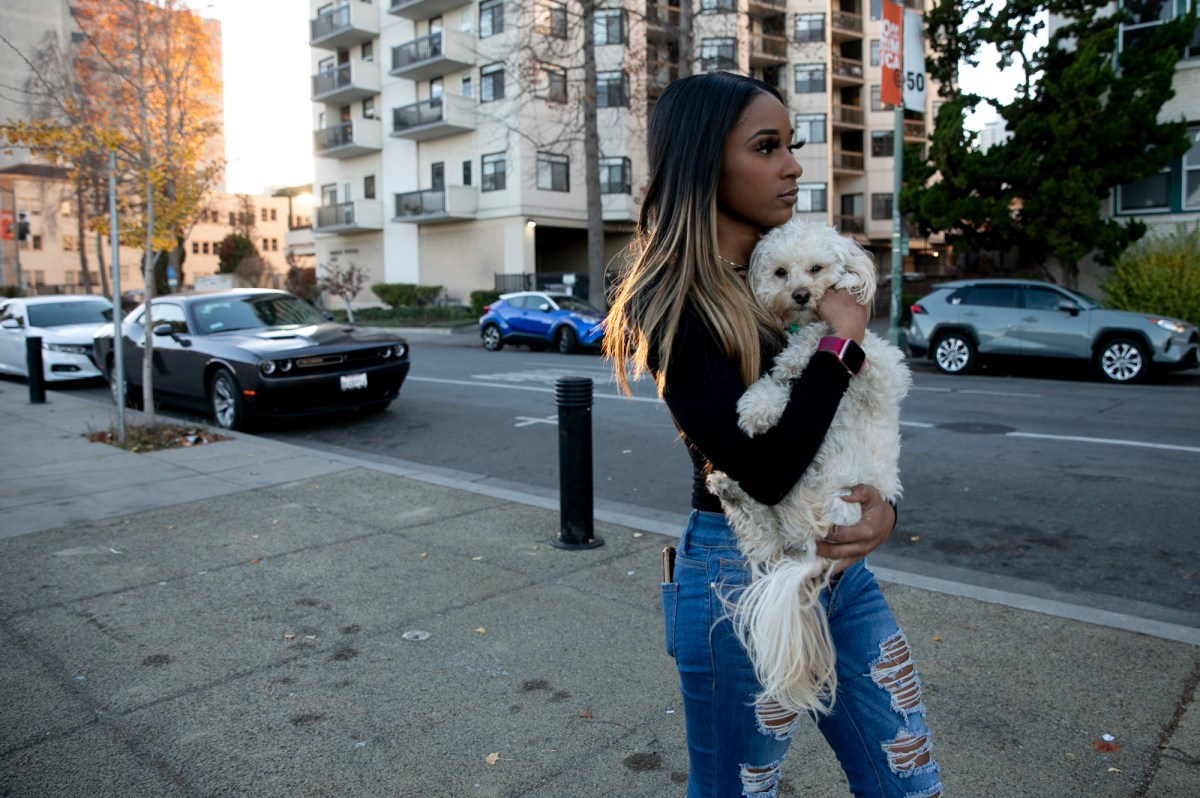 Jhonae Mazique carries her dog, Simba, to her friend's apartment near Lake Merritt where she's currently staying after losing her housing earlier this year, in Oakland on Dec. 8, 2020. Photo by Anne Wernikoff for CalMatters
