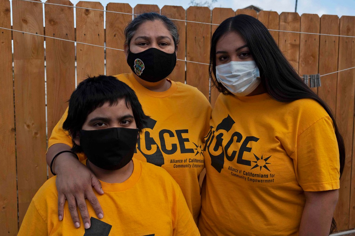 Patricia Mendoza stands with her two children, Erik and Alejandra in the backyard of their Imperial Beach apartment on Dec. 10, 2020. Photo by Tash Kimmell for CalMatters.