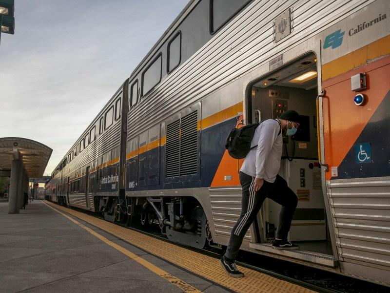 Un pasajero se sube a un tren con destino a Bakersfield en la estación Emeryville Amtrak el 16 de diciembre de 2020. Foto de Anne Wernikoff para CalMatters