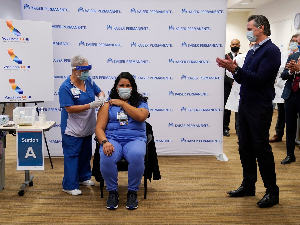ICU nurse Helen Cordova receives the Pfizer-BioNTech COVID-19 vaccine as Gov. Gavin Newsom watches at Kaiser Permanente Los Angeles Medical Center on Dec. 14, 2020. Photo by Jae C. Hong, AP Photo/Pool