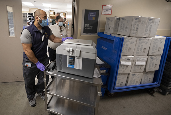 Pharmacy technician Joel Miyake and pharmacist Erin St. Angelo transfer 50 bottles of the Pfizer-BioNTech from the main pharmacy to the room where they will be administered to the most at-risk employees at the UC Davis Medical Center on Dec. 15, 2020. Photo courtesy of UC Davis Health