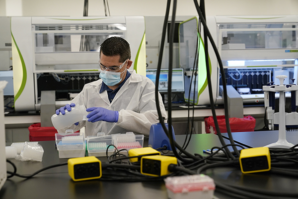 A technician conducts COVID-19 tests at a new facility on Oct. 30, 2020, in Valencia. The state is working with corporate partner PerkinElmer to run the lab which will enable the state to process an additional 150,000 COVID-19 tests per day. Photo by Marcio Jose Sanchez, AP Photo/Pool