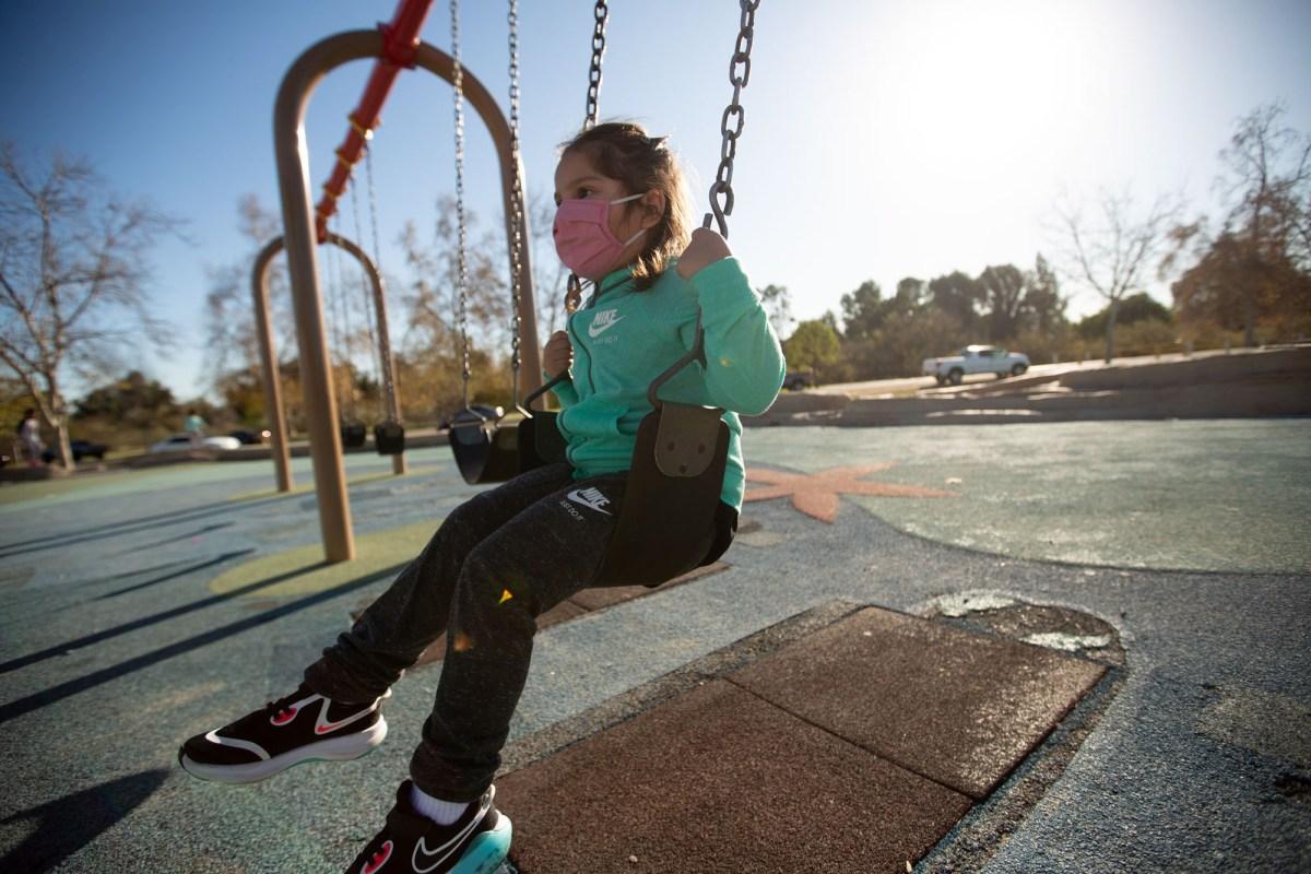 Mae Villanueva, de 4 años, juega en el parque Lake Balboa en Van Nuys el 20 de enero de 2021. A los padres de Mae les preocupa que sin instrucción en persona se atrasará en la lectura. Foto de Shae Hammond para CalMatters