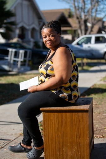 Deborah Bell-Holt sits in front of her house in Jefferson Park near Downtown Los Angeles on Jan. 21, 2021, holding her water and power bill. Photo by Shae Hammond for CalMatters