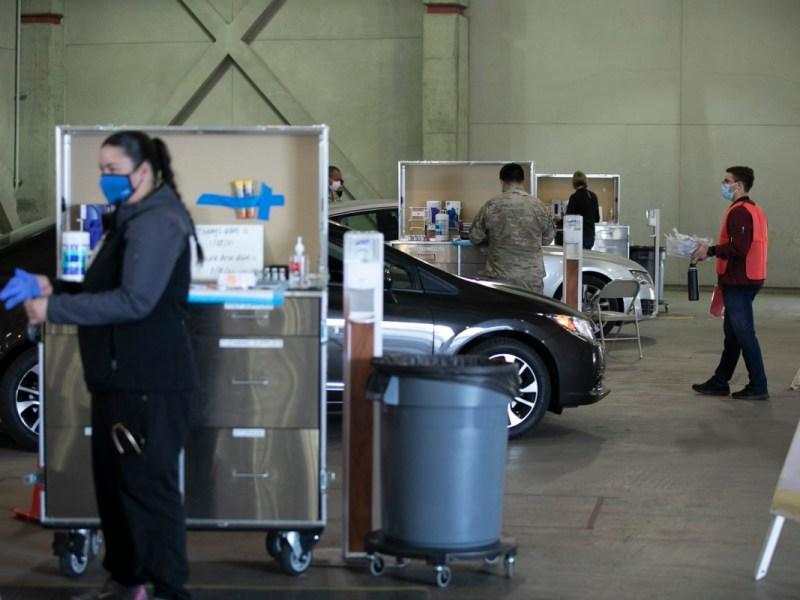 Los miembros de la Guardia Nacional y el personal médico administran las vacunas COVID a los trabajadores de la salud en un sitio de distribución de autoservicio en Cal Expo en Sacramento el 21 de enero de 2021. Foto de Anne Wernikoff, CalMatters