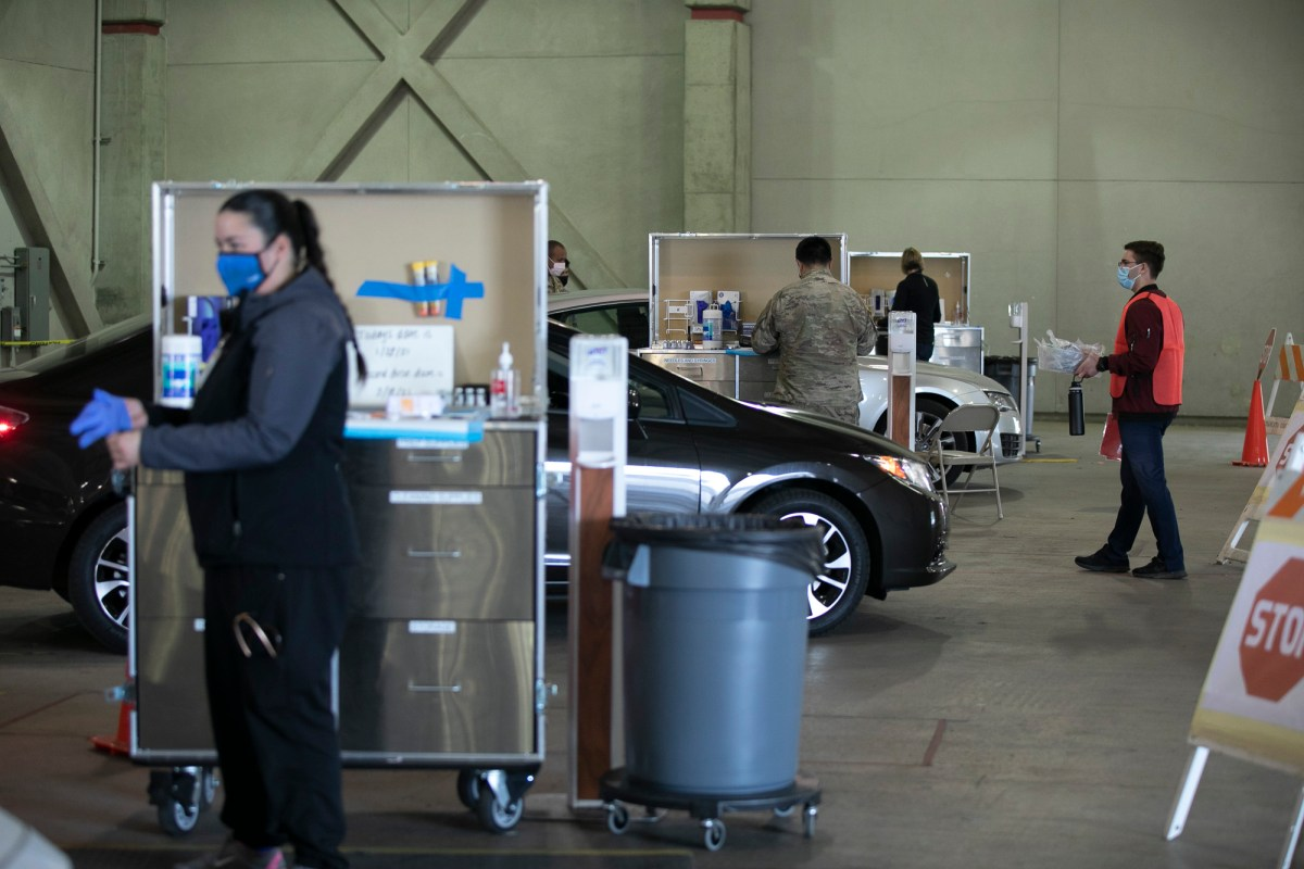 National Guard members and medical personnel administer COVID vaccines to health care workers at a drive through distribution site at Cal Expo in Sacramento on Jan. 21, 2021. Photo by Anne Wernikoff, CalMatters