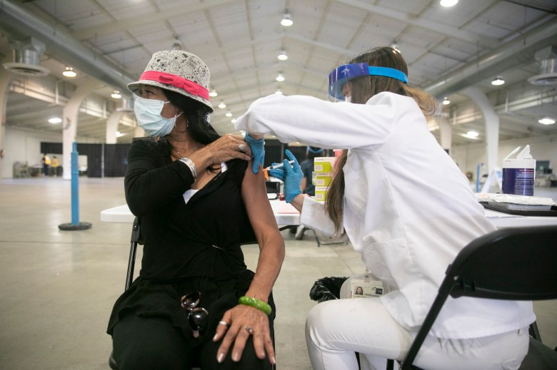 UCSF pharmacy student Connie Chen, right, administers a flu vaccine to Yvonne Predium, left, during a free drop-in flu shot clinic at Santa Clara County fair grounds on Oct. 17, 2020. Photo by Anne Wernikoff, CalMatters