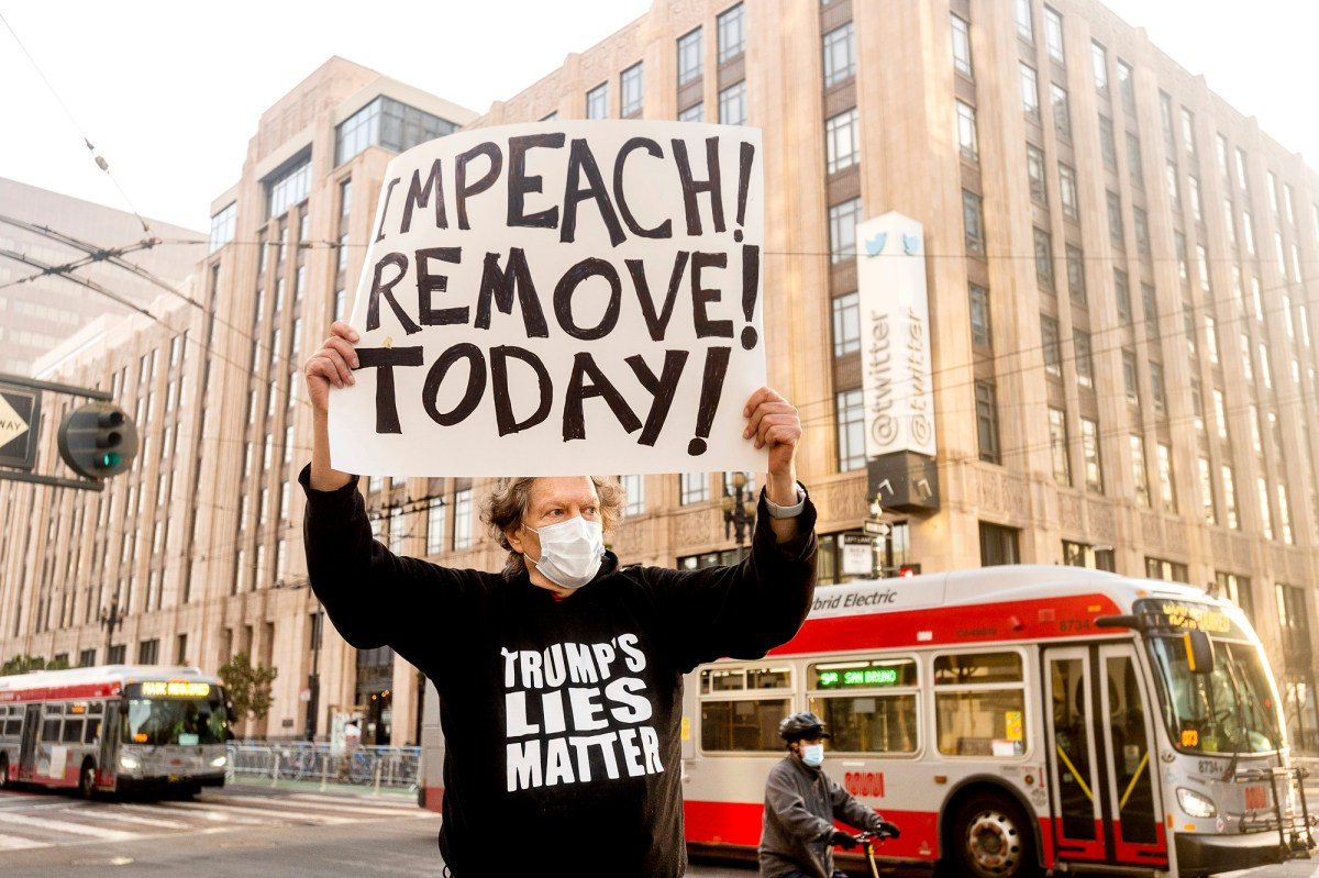 Kenneth Lundgreen holds a sign against President Donald Trump outside of Twitter headquarters on Jan. 11, 2021, in San Francisco. Police officers erected barricades and staged for a possible conservative protest Monday morning. Photo by Noah Berger, AP Photo