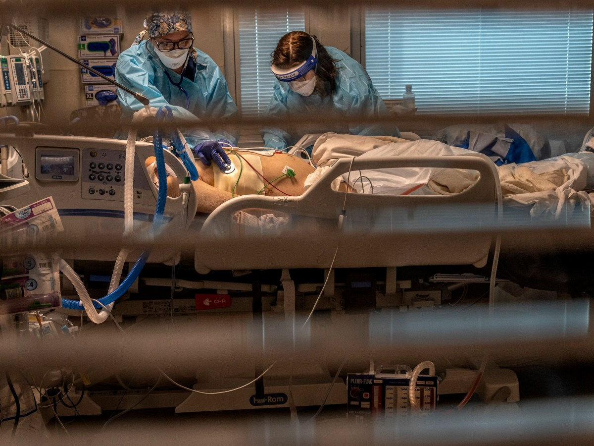 Phlebotomist lab assistant Jennifer Cukati, right, and Registered Nurse Carina Klescewski, left, care for a COVID-19 patient inside the Sutter Roseville Medical Center ICU in Roseville on Dec. 22, 2020. California became the first state to record 2 million confirmed coronavirus cases, reaching the milestone on Christmas Eve as close to the entire state was under a strict stay-at-home order and hospitals were flooded with the largest crush of cases since the pandemic began. Photo by Renee C. Byer, The Sacramento Bee via AP/Pool