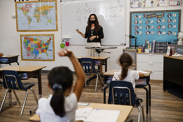 Second and third grade teacher Kylie Shannon, center, answers questions from students during the first day of school at Sunnyvale Christian School in Sunnyvale on Thursday, Aug. 27, 2020. Photo by Randy Vazquez, Bay Area News Group