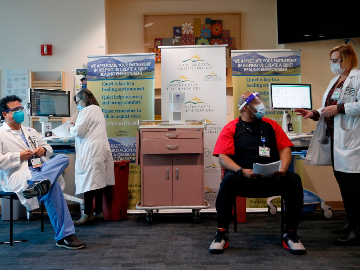 Dr. Sergio Urcuyo, chair of the Department of Hospital Medicine, left, prepares to receive a Covid-19 vaccine from Registered Nurse Kathy Ferris, left, as Infection Prevention and Control Program Manager Holly Longmuir, explains the procedure to Licensed Vocational Nurse Henri K. at the Contra Costa Regional Medical Center in Martinez, Calif., on Dec.15, 2020. Photo by Jane Tyska, Bay Area News Group