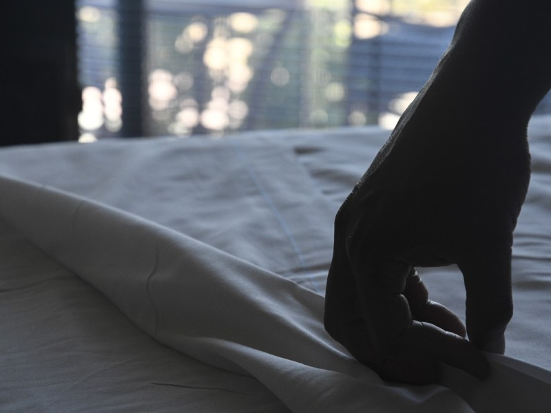 John adjusts the covers on his massage table. Photo by Ayrton Ostly, The Salinas Californian