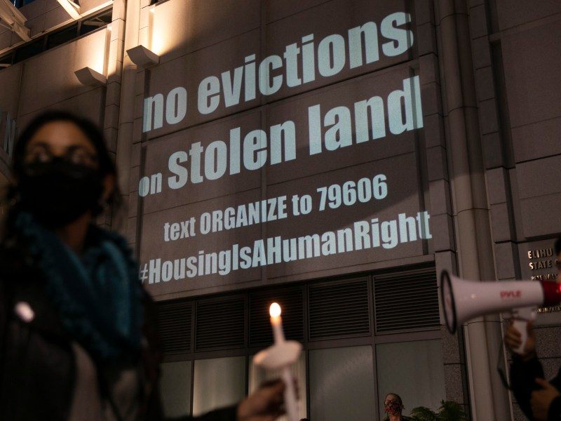Housing activists and rent strikers participate in a vigil for tenants who they say will not be covered by Gov. Gavin Newsom's rent relief plan at the Elihu M. Harris, State of California office building in Oakland on Jan. 29, 2021. Photo by Anne Wernikoff, CalMatters