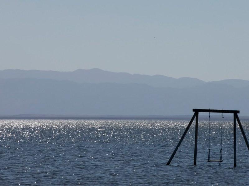 Un juego de columpios se encuentra solo en el Mar de Salton. Los funcionarios estatales están ayudando a financiar proyectos experimentales para extraer valioso litio de la salmuera del lago. Foto de Shae Hammond para CalMatters