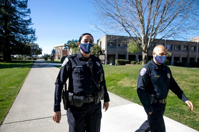 Los agentes de policía del campus Tejinder Arurkar, izquierda, y el teniente Omar Miakhail caminan por el campus de Cal State East Bay en Hayward el 17 de febrero de 2021. CSUEB tiene uno de los departamentos de policía de campus más diversos del estado. Foto de Anne Wernikoff, CalMatters