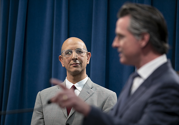 California Health and Human Services Agency Secretary Dr. Mark Ghaly looks on as Gov. Gavin Newsom gives a press conference following the first COVID-19 death in California on March 4, 2020. Photo by Anne Wernikoff for CalMatters