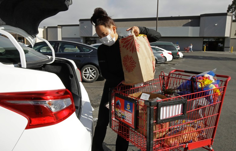 Instacart worker Saori Okawa loads groceries into her car for home delivery in San Leandro on July 1, 2020. Delivery drivers, grocery runners and freelancers need to pay income and self-employment tax on their earnings, which can amount to 30% of their earnings. Photo by Ben Margot, AP Photo