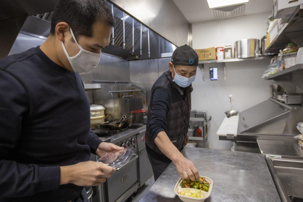 Dan Zhao, izquierda, y su padre Keguang Zhao empaquetan un Kung Pao Tofu en Cozy Wok, un restaurante chino vegetariano de entrega y comida para llevar, en Oakland, el jueves 28 de enero de 2021. Dan Zhao, gerente de producto en una empresa de software con sede en San Francisco y su padre Keguang Zhao abrieron el restaurante, que está abierto por las noches y los fines de semana, durante una pandemia. Foto de Anda Chu, Bay Area News Group