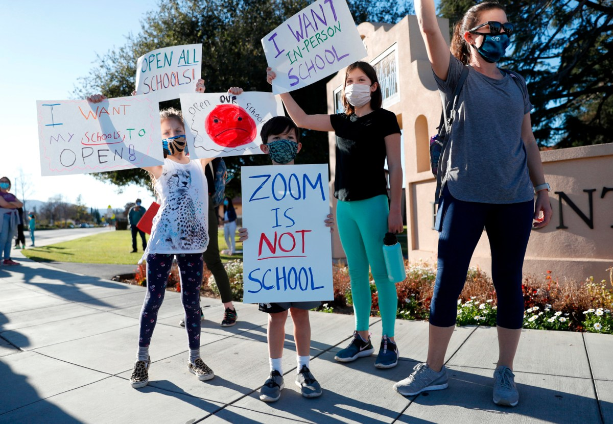 Jill Borges, far right, a teacher at Cupertino High School, protests school closings in the Cupertino and Sunnyvale school districts with her three children, from left to right, Emry, 9, Cruz, 7, and Brooklyn, 9, in front of Fremont High School in Sunnyvale on Feb. 23, 2021. Photo by Nhat V. Meyer, Bay Area News Group