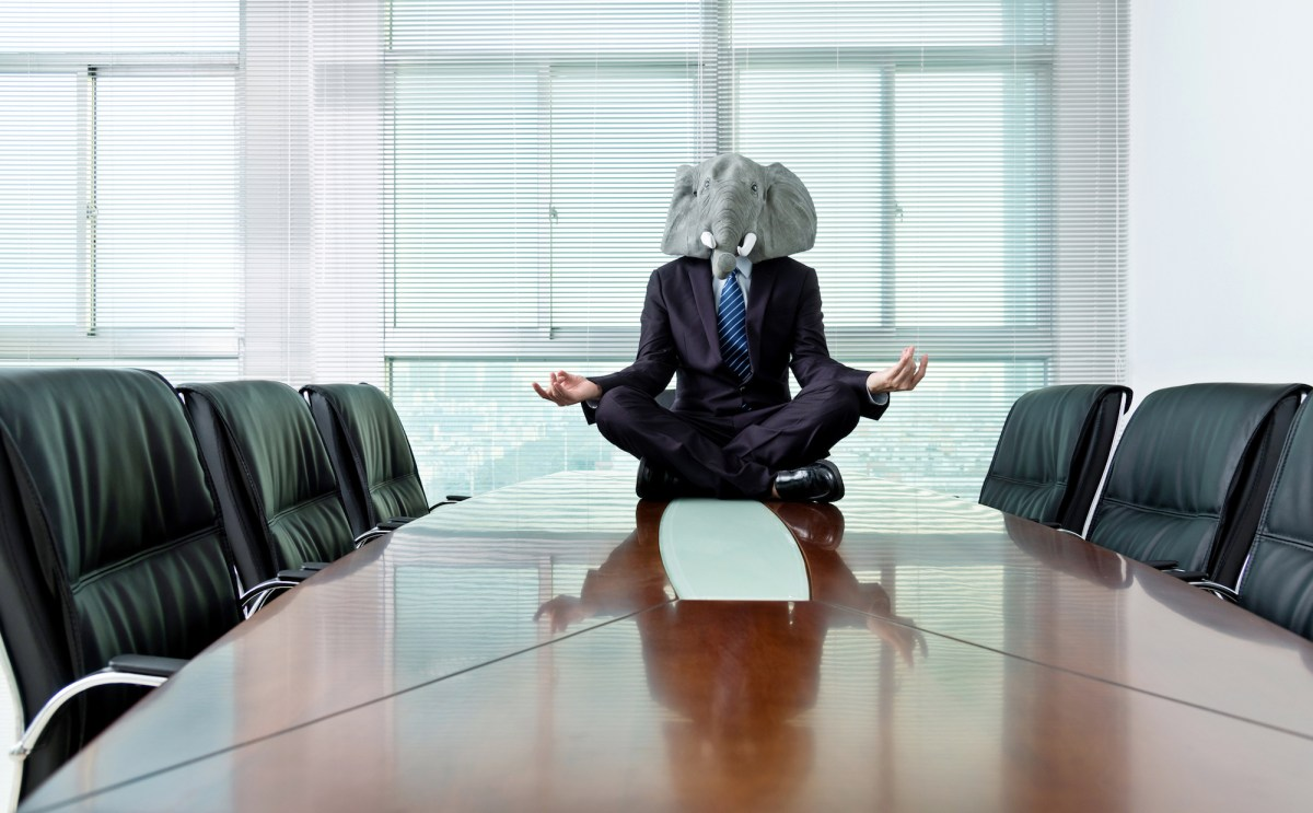 A man wearing an elephant mask sits meditating in a conference room. The California Republican Party, in its first state convention since President Trump was voted out of office, did everything possible to maintain unity. Zoom helped. Image via iStock