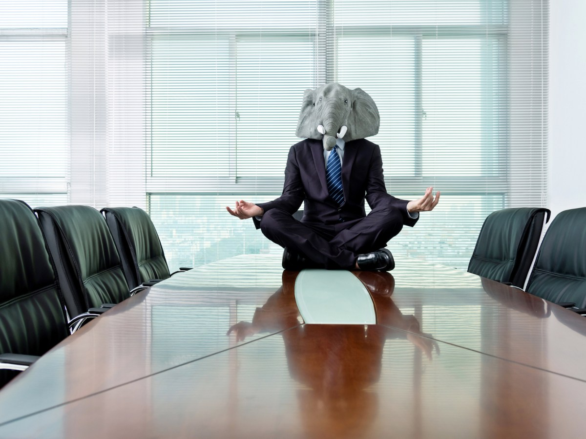 A man wearing an elephant mask sits meditating in a conference hall.  The California Republican Party, at its first state convention since President Trump was removed from office, has done everything possible to maintain unity.  Zoom helped.  Image via iStock