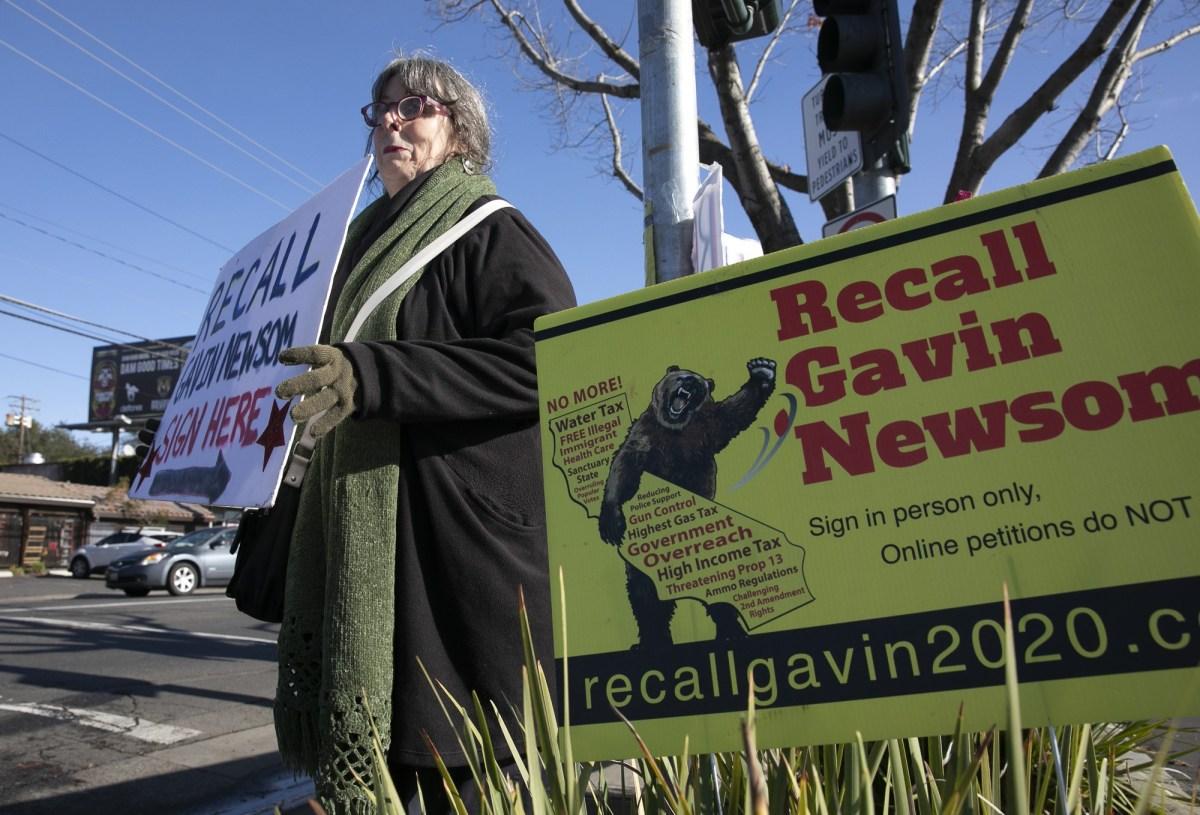La voluntaria de Destituyen Newsom, Kerin Kay, sostiene un cartel durante un evento de firma de peticiones en un Save Mart en Sacramento el 5 de enero de 2021. Foto de Anne Wernikoff, CalMatters