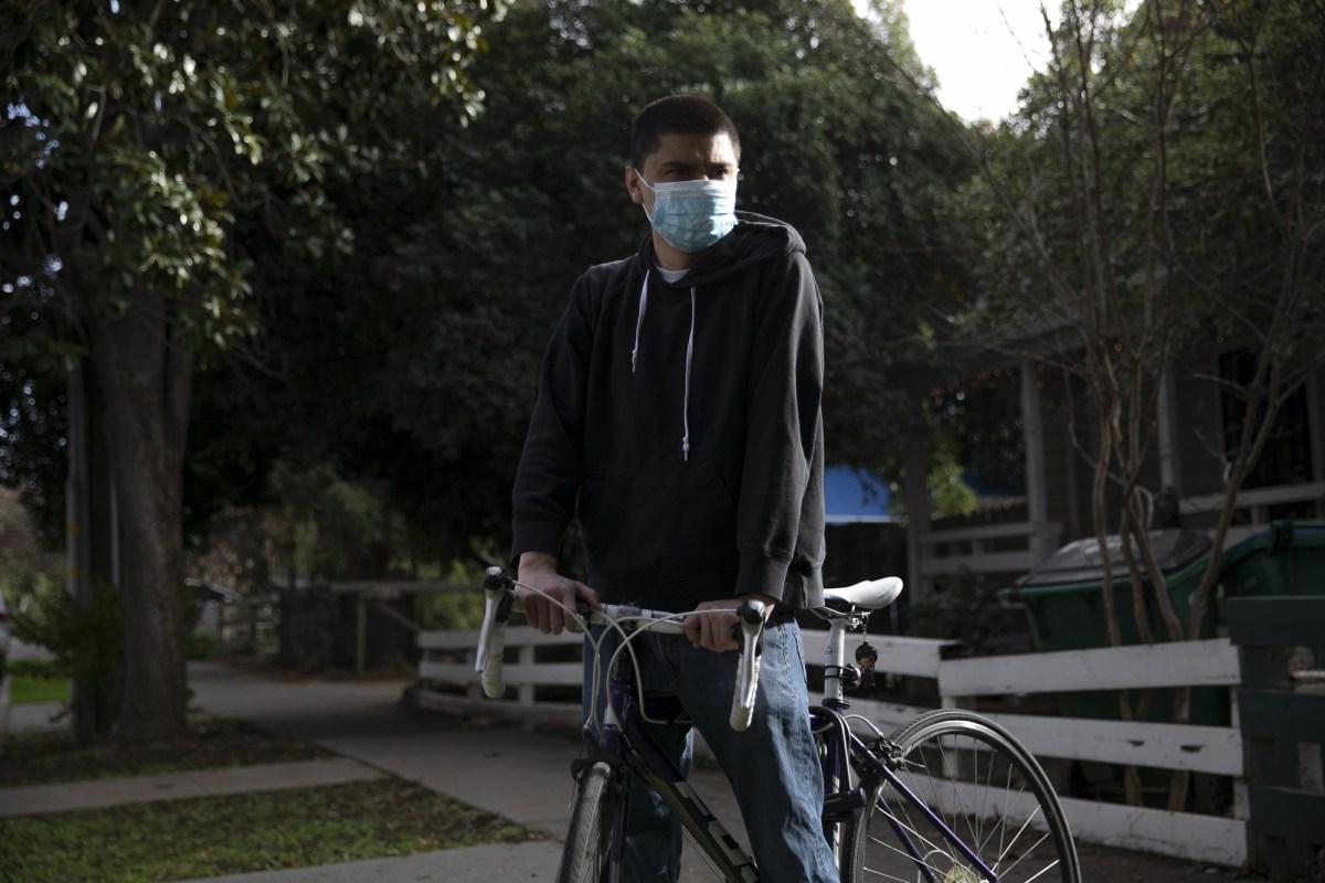 El estudiante de tercer año de CSU Chico, Julian Mendoza, está parado con su bicicleta cerca de donde fue detenido por la policía de la universidad, a casi una docena de cuadras del campus, por andar en bicicleta en el campus, el 16 de febrero de 2021. Foto de Anne Wernikoff, CalMatters