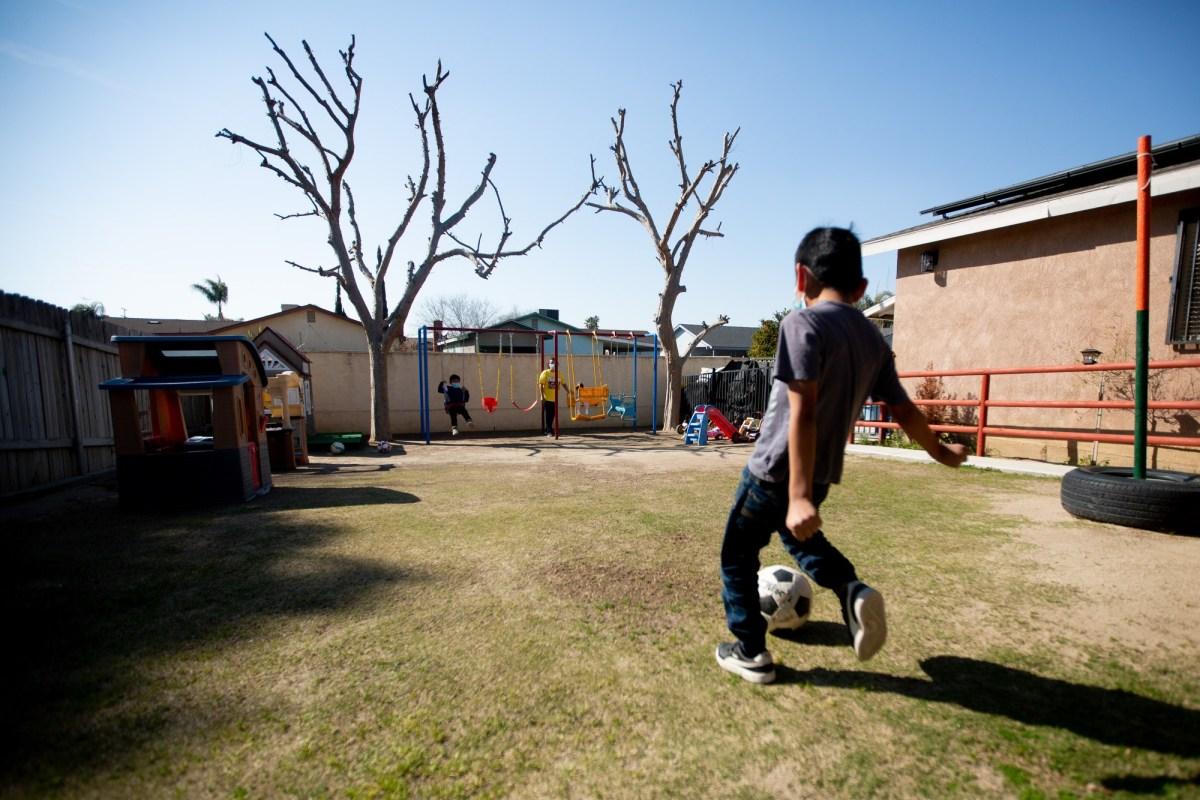 Los niños juegan en el patio trasero de la casa de Ana Ballesteros donde dirige una guardería en Delano el 26 de febrero de 2021. Foto de Shae Hammond para CalMatters
