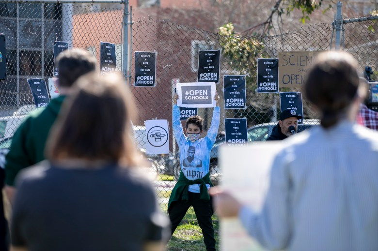 Micah Castillo, 10, holds up a sign while his father, David Castillo, speaks at the podium during a rally to reopen Oakland public school on Feb. 28, 2021. Photo by Anne Wernikoff, CalMatters
