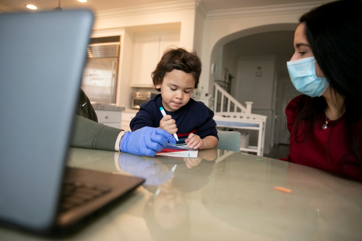 Jonathan, 4, works on an art project with help from his therapist, left, and mother, Natalia Acosta, right, during online preschool at his him in Tracy on March 3, 2021. He is among California's special-needs students who have faced special challenges during the pandemic. Photo by Anne Wernikoff, CalMatters